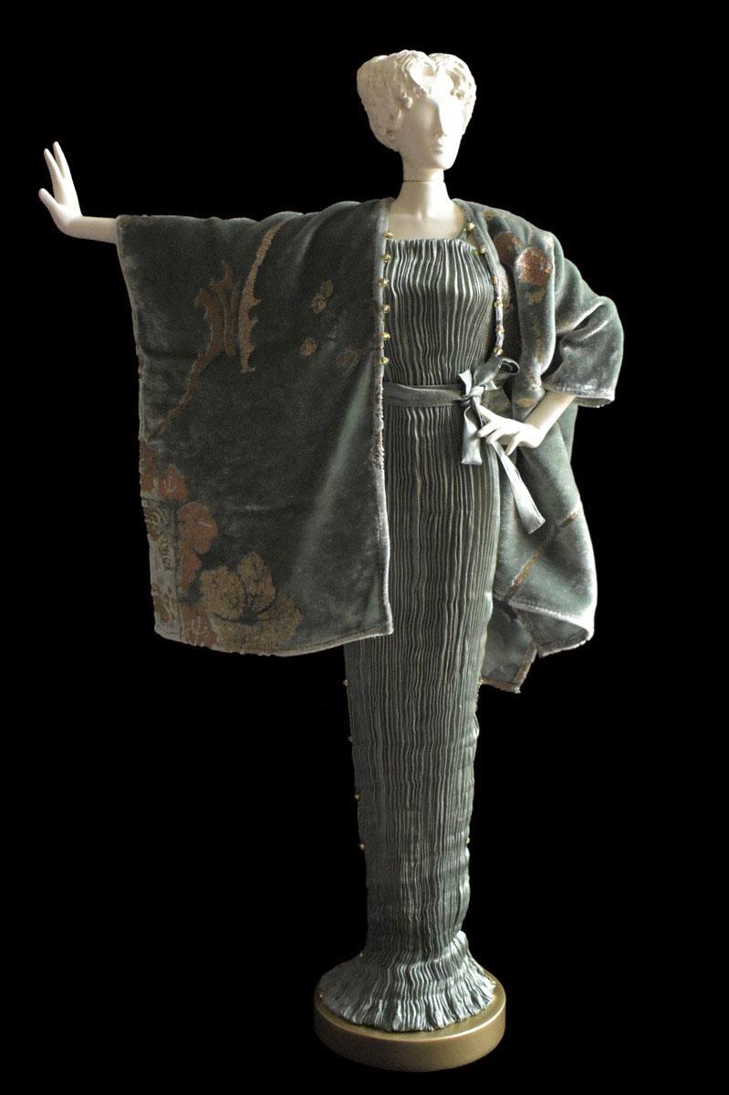 Figurine féminine Diva habillée d'une robe Pretty en soie plissée gris sauge et d'un manteau du soir en velours imprimé - Roman